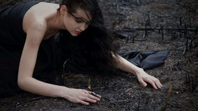 People and dying nature. Ecology concept. Sad girl sitting on the burned-out land. Concept of environmental disaster. Global problems with ecology. Young stock video