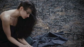 People and dying nature. Ecology concept. Sad girl sitting on the burned-out land. Concept of environmental disaster. Global problems with ecology. Young stock video footage