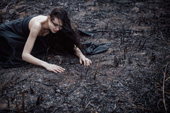 People and dying nature. Ecology concept. Sad girl sitting on the burned-out land. Concept of environmental disaster. Global problems with ecology. Young Stock Images