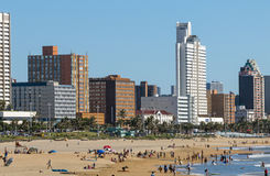 People on Early Morning Beach Against City Skyline Stock Photo