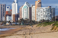 People on Early Morning Beach Against City Skyline Royalty Free Stock Photography