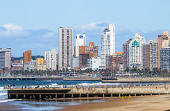 People on Early Morning Beach Against City Skyline Royalty Free Stock Images