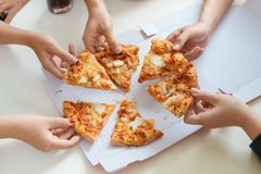 People eat fast food. Friends hands taking slices of pizza Royalty Free Stock Photography