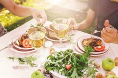 People eat in the garden at the table. Dinner concept with wine in the fresh air. Fish and salads with vegetables and herbs. Mediterranean Kitchen. Horizontal stock photos