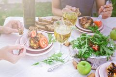People eat in the garden at the table. Dinner concept with wine in the fresh air. Grilled sea fish and salads with vegetables and. Herbs. Mediterranean Kitchen royalty free stock photos