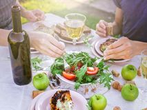 People eat in the garden at the table. Dinner concept with wine in the fresh air. Grilled sea fish and salads with vegetables and. Herbs. Mediterranean Kitchen stock photos