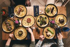 People eat healthy food and drink alcohol, top view. Friends Company gathering for Christmas or New Year party dinner at festive table. Flat-lay of human hands stock image