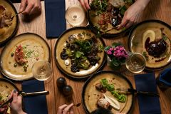 People eat healthy meals and drink alcohol festive table. Served for party, top view. Friends celebrate with organic food on wooden table Happy company having stock image