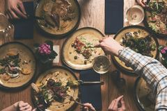 People eat healthy meals and drink alcohol festive table. Served for party, top view. Friends celebrate with organic food on wooden table Happy company having stock photography