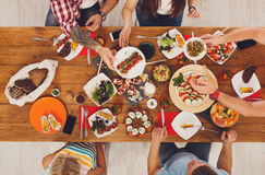 People eat healthy meals at festive table dinner party. People eat healthy meals at served festive table served for party. Friends celebrate with organic food on Stock Photo