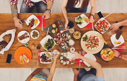 People eat meals drink alcohol at festive table dinner party Royalty Free Stock Photography