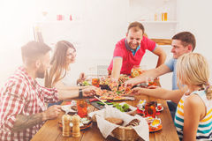 People eat pizza at festive table dinner party Royalty Free Stock Image
