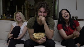 People eat popcorn and watch funny entertainment TV show and find it very hilarious stock footage