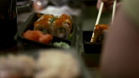 People eat sushi and rolls Japanese chopsticks.  stock video