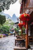 People and eatery on alley in Yangshuo town. YANGSHUO, CHINA - MARCH 30, 2017: people and eatery on alley in Yangshuo town in spring. Town is resort destination Stock Photography