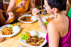 People eating in Asia restaurant. Young people eating in Asia restaurant stock photography