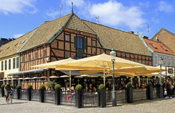 People are eating in cafe located at medieval house on the market place Lilla Torg Royalty Free Stock Image