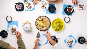 People eating dessert and drinking tea, top view Stock Photo
