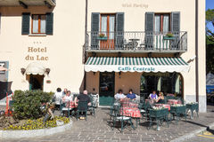 People eating and drinking on a restaurant of Menaggio, Italy. Menaggio, Italy - 10 March 2017: people eating and drinking on a restaurant of Menaggio, Italy Royalty Free Stock Photos
