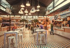 People eating food inside modern style city market with fast-food stores and retro interior royalty free stock photography