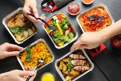 Free People Eating From Lunchboxes At Grey Table. Healthy Food Delivery Stock Photography - 161242402