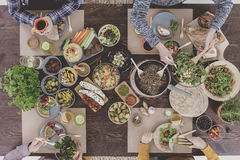 People eating healthy meal. People sitting beside wooden table, eating healthy meal Stock Image
