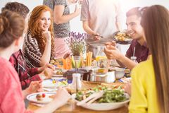People eating healthy organic dishes. Vegetarian food concept, young people sitting around the table eating freshly made vegetable salads and healthy organic Royalty Free Stock Photos