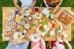 People eating italian dinner. High angle of people eating italian dinner at a table with pizza, pastry and bread-sticks royalty free stock image