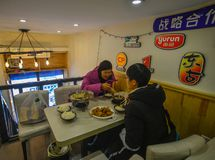 People eating at local restaurant. Harbin, China - Feb 22, 2018. People eating at local restaurant in Harbin, China. Harbin is largest city in the northeastern stock image