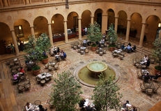 People eating lunch in museum courtyard. People eating lunch in a museum courtyard with Roman columns,arches, and a fountain. Taken in February 2016 Stock Photography