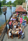 People eating out by the riverside in the sunshine. stock photo