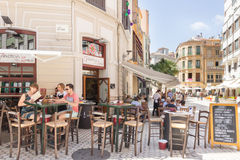 People eating outdoors in a restaurant in Malaga. Malaga, Spain-August 26th 2015: People eating outside a restaurant. Al fresco dining is very popular both at royalty free stock image