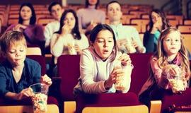 People eating popcorn in cinema Stock Photo