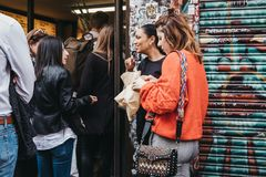 People eating and queuing to buy bagels from a famous Beigel Shop in Brick Lane, London, UK royalty free stock image