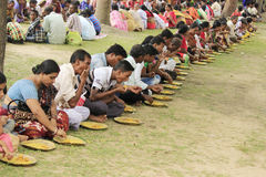 People are eating in a row during Bengali cultural festival.