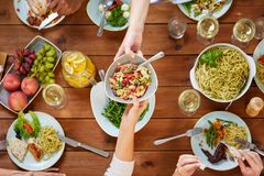 People eating salad at table with food stock photos