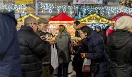 People eating sausages at Christmas market in Bucharest Royalty Free Stock Photo