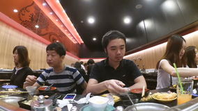 People eating sushi from sushi conveyor belt buffet at japanese restaurant stock video