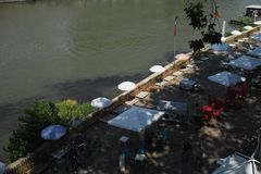 Outdoor cafe seating on the banks of the River Tiber, Rome, Italy. People eating and walking through outdoor cafe with white umbrellas on the banks of the River stock photo
