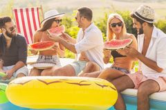 People eating watermelon by the pool stock images