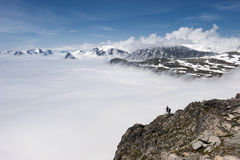 People on the edge of mountain peak above the clouds, view from the mountain Dalsnibba to Geirange Stock Image