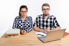 People and education concept - Two sad students dressed in plaid shirt sitting at a table. People and education concept - Two students dressed in plaid shirt royalty free stock photo