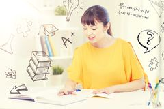 Happy asian young woman student learning at home. People, education, high school and learning concept - happy asian young woman student with book and notepad Royalty Free Stock Photography