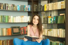 People, education and knowledge concept - Woman reading book in library stock image