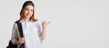 People, education and studying concept. Attractive delighted female pupil, wears formal white shirt, black cap, carries rucksack,. Indicates at blank copy space royalty free stock images