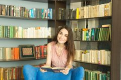 People, education and university concept - young student woman with a book in library.  stock photo