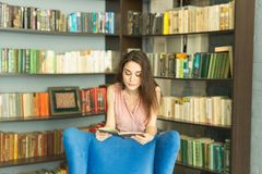 People, education and university concept - young student woman with a book in library.  stock image