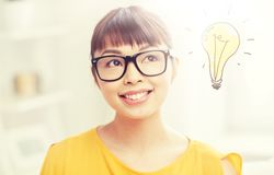 Asian woman in glasses with light bulb doodle. People, education, vision and portrait concept - happy asian young woman or teenage student girl in glasses over Stock Photography