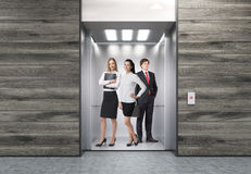 People in elevator in corridor with wooden walls Stock Image