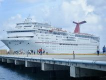 Cruise Ship Port Call. People embark on adventures, hikes and shopping as they depart a pleasure cruise ship as it makes a port of call to an exotic location stock photography